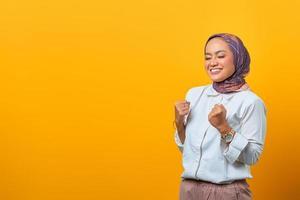 Mulher asiática animada fechou os olhos e comemorando a vitória sorrindo foto