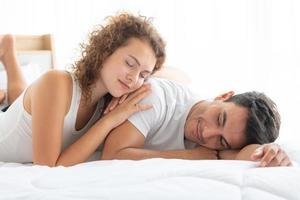 casais felizes relaxando no quarto branco do apartamento foto