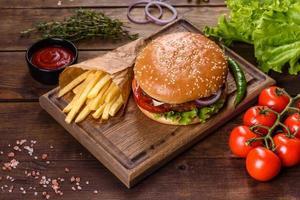 hambúrguer artesanal de carne e batatas fritas em um fundo preto foto