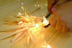 homem, a mão inicia uma fogueira com sílex de magnésio fogo de aço foto