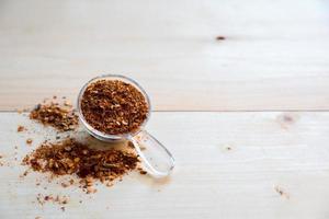 tempero de pimenta caiena em colher na mesa de madeira foto