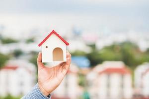 mão segurando a casa de maquete. seguro de empréstimo imobiliário foto