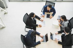 Equipe de executivos asiáticos analisando estatísticas financeiras. foto