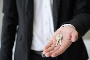 feche a mão do negócio, segurando a chave em casa. foto