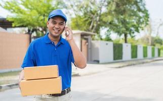 entregador azul segurando a caixa de papelão do pacote e falando no telefone. foto