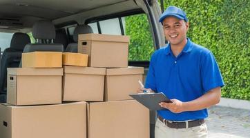 entregador azul pega a caixa de papelão do pacote no caminhão foto