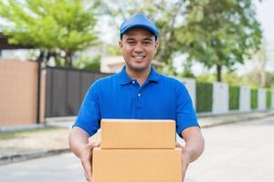 entregar homem de uniforme azul e caixa de papelão de pacote foto