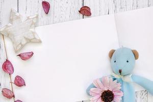 mesa de madeira pintada de branco, pétalas de flores roxas, urso, boneca, estrela, artesanato foto