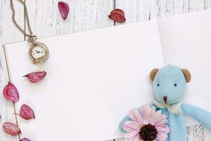 mesa de madeira pintada de branco, pétalas de flores roxas, urso, boneca, relógio de bolso foto