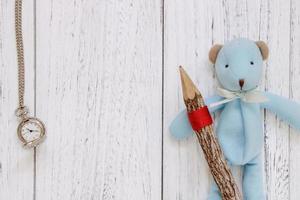 Boneca urso azul com mesa de madeira pintada de branco segurando um relógio de bolso foto