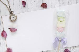 Relógio de bolso de algodão doce com pétalas de flores em papel de mesa de madeira pintada de branco foto