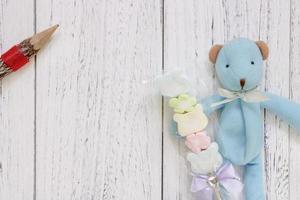 Boneca de urso azul com mesa de madeira pintada de branco segurando lápis de algodão doce foto