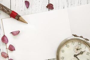 mesa de madeira pintada de branco, pétalas de flores, lápis despertador vintage foto