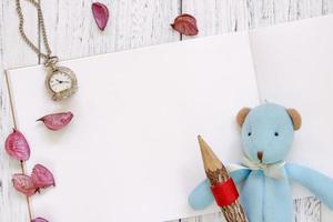 papel com um brinquedo, lápis, relógio e pétalas foto