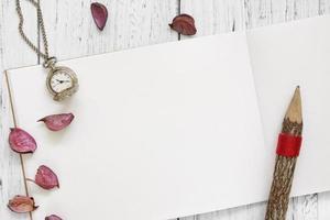 papel com relógio, pétalas e lápis foto
