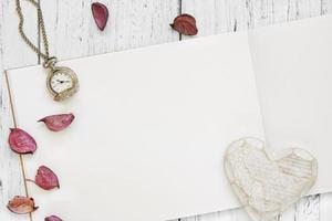 mesa de madeira pintada de branco pétalas de flores roxas relógio de bolso e coração artesanal foto
