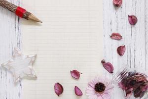 papel com estrela, lápis e pétalas foto