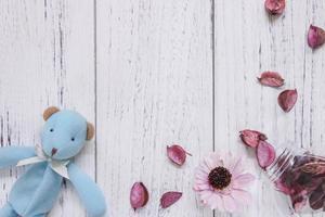brinquedo e pétalas em madeira branca foto