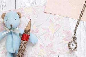 papel floral com brinquedo, lápis e relógio foto
