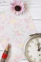 papel floral com lápis, flor e relógio foto