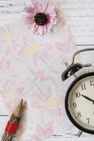 papel floral com flor, lápis e relógio foto