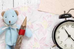 papel floral com um brinquedo, lápis e relógio foto