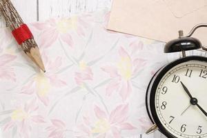 papel floral com lápis e relógio foto