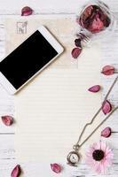papel com telefone, relógio e pétalas foto