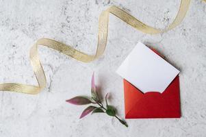 um cartão em branco com um envelope vermelho e uma folha é colocado em um fundo branco foto