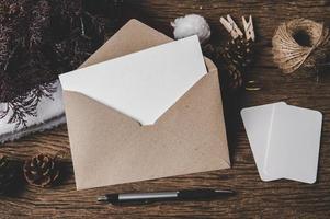 envelope, cartão em branco e uma caneta são colocados na madeira. foto