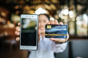 telefone inteligente e cartão de crédito com mulher disponível foto