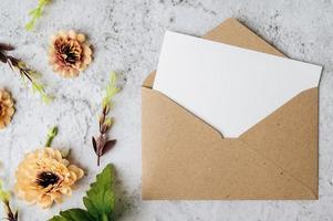 um cartão em branco com um envelope e uma flor é colocado em um fundo branco foto