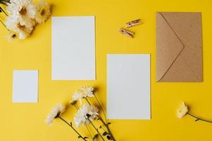 cartão em branco com envelope e flor é colocado em fundo amarelo foto