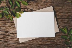 um cartão em branco é colocado em um envelope e uma folha com fundo de madeira foto