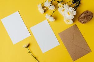 um cartão em branco com envelope e flor é colocado em fundo amarelo foto
