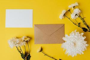um cartão em branco com envelope e flores é colocado em fundo amarelo foto