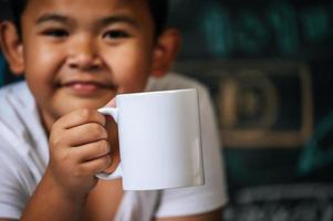 criança sentada e segurando um copo na sala de aula foto