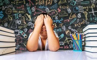 criança sentada com as mãos fecha os olhos na sala de aula foto