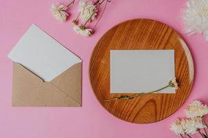envelope pardo, flor e cartão em branco na placa de madeira foto