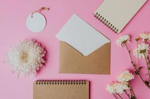 envelope marrom, etiqueta, caderno com cartão em branco e flor foto