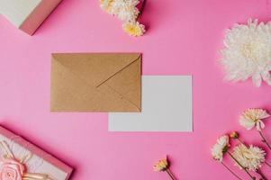envelope marrom, caixa de presente rosa com cartão em branco e flor foto