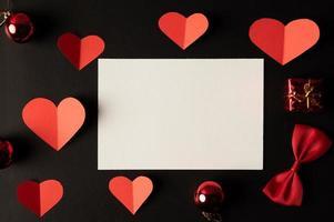 papel branco e papel de coração vermelho colados em um fundo preto. foto