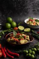 curry de porco verde em uma tigela marrom com especiarias em um cimento preto foto