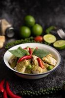 curry de porco verde em uma tigela branca com especiarias em um cimento preto foto