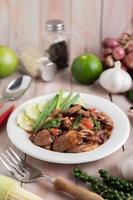 manjericão santo arroz frito com coração de frango em um piso de madeira branco. foto