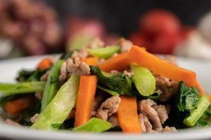 Misture a couve frita e as cenouras com a carne de porco picada em um prato branco. foto