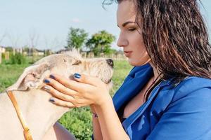 jovem mulher atraente brincando com seu cachorro no parque foto