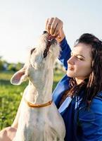 jovem mulher atraente alimentando seu cachorro no parque foto