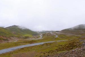 estrada ao redor da montanha, dia nublado na província de qinghai, china foto