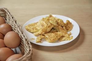 omeletes em chapa branca, cesta de ovos na mesa da cozinha em casa. foto